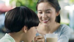 Sluit omhoog van Aziatische moeder die haar zoon een cake voeden bij openluchtplaatsing in langzame motie stock videobeelden