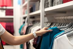 Sluit omhoog van Aziatische vrouwenhand die of toevallige blauwe kleurent-shirt op rek kiezen bij jonge klerenwinkel bij warenhui stock fotografie