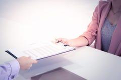 Sluit omhoog van baangesprek die zich bij vrouw het overhandigen concentreren hervatten met het bureau royalty-vrije stock afbeeldingen