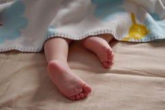 Sluit omhoog van babyvoeten glurend uit deken Het kind slaapt royalty-vrije stock foto's