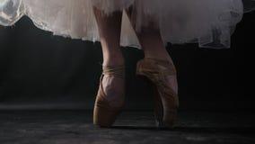 Sluit omhoog van balletdanser aangezien zij praktijkenoefeningen op donkere stadium of studio Vrouwen` s voeten in pointeschoenen stock videobeelden