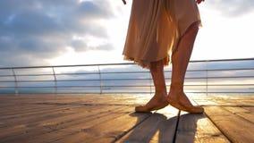 Sluit omhoog van balletdanser` s voeten aangezien zij in pointeoefeningen op de dijk dichtbij overzees, zonsopgangachtergrond pra stock video