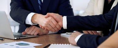 Sluit omhoog van bedrijfsmensen die handen schudden bij vergadering of onderhandeling in het bureau De partners zijn tevreden omd stock afbeelding