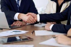 Sluit omhoog van bedrijfsmensen die handen schudden bij vergadering of onderhandeling in het bureau De partners zijn tevreden omd stock fotografie