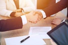 Sluit omhoog van bedrijfsmensen die handen schudden bij vergadering of onderhandeling in het bureau De partners zijn tevreden omd royalty-vrije stock afbeeldingen