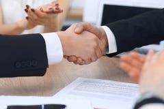 Sluit omhoog van bedrijfsmensen die handen schudden bij vergadering of onderhandeling in het bureau De partners zijn tevreden omd stock foto's