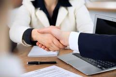 Sluit omhoog van bedrijfsmensen die handen schudden bij vergadering of onderhandeling in het bureau De partners zijn tevreden omd stock foto