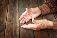 Sluit omhoog van bejaarde mannelijke handen op houten lijst Stock Afbeeldingen