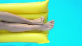 Sluit omhoog van benen bij het opblaasbare matras spelen met water in pool, vakantie stock footage