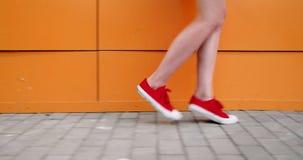 Sluit omhoog van benen van een jonge vrouw die het donkerrode tennisschoenen lopen dragen stock footage