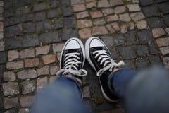 Sluit omhoog van benen in zwarte keds die op asfalt liggen Stock Afbeeldingen
