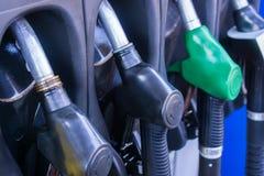 Sluit omhoog van benzinepomppijpen in een benzinestation stock afbeelding