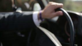 Sluit omhoog van bestuurders` s hand met armband op het roer Blauwe hemel en auto stock videobeelden