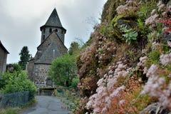 Sluit omhoog van bloemen en Kerk van St Peter van vic-sur-Cere Royalty-vrije Stock Afbeeldingen