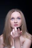 Sluit omhoog van blond meisje met veer op zwarte Stock Foto's