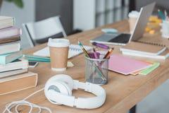 sluit omhoog van boeken, hoofdtelefoons, koffie, voorbeeldenboeken en laptop royalty-vrije stock foto