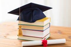 Sluit omhoog van boeken met diploma en baret Royalty-vrije Stock Foto's