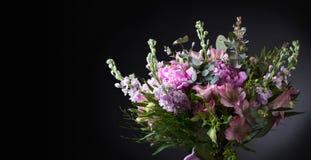 Sluit omhoog van boeket met roze pioenen op zwarte achtergrond stock fotografie