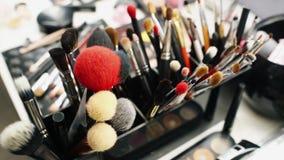 Sluit omhoog van borstels, make-uphulpmiddelen op de lijst in de kleedkamer stock footage