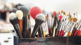 Sluit omhoog van borstels, make-uphulpmiddelen op de lijst in de kleedkamer stock videobeelden