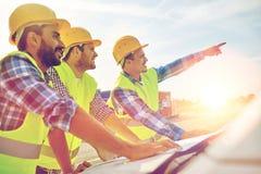 Sluit omhoog van bouwers met blauwdruk op autokap royalty-vrije stock afbeelding