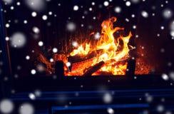 Sluit omhoog van brandhout het branden in open haard en sneeuw royalty-vrije stock foto's