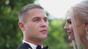 Sluit omhoog van bruidegom en bruid Mooi huwelijkspaar in het park Modieuze jonggehuwden stock videobeelden