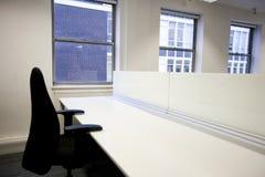 Sluit omhoog van bureaustoel en leeg bureau door venster stock foto