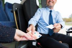 Sluit omhoog van buschauffeur verkopend kaartje aan passagier stock foto