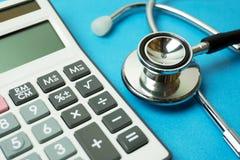 Sluit omhoog van calculator en stethoscoop op blauwe achtergrond Royalty-vrije Stock Afbeelding
