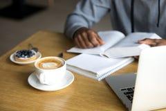 Sluit omhoog van cappuccinokop aan zwarte koffiebezoeker die wordt gediend royalty-vrije stock fotografie
