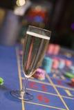 Sluit omhoog van champagneglas op roulettelijst Royalty-vrije Stock Afbeelding