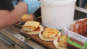 Sluit omhoog van chef-kok` s handen die burgers voorbereiden stock footage