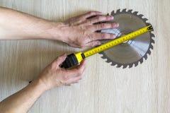 Sluit omhoog van cirkelzaagblad voor houten het werk en arbeidershandverstand Stock Foto's