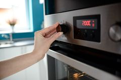 Sluit omhoog van controle van de de hand de plaatsende temperatuur van de vrouw op oven Royalty-vrije Stock Foto's
