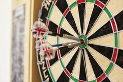 Sluit omhoog van Dartboard met Drie Pijltjes in Bullseye Stock Foto