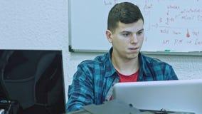 Sluit omhoog van de aantrekkelijke jonge mens gebruikend computer op zijn werkende plaats Op groene achtergrond stock video