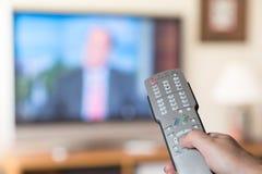 Sluit omhoog van de afstandsbediening van TV met televisie Royalty-vrije Stock Foto