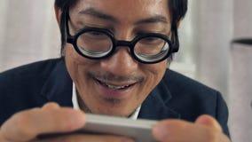 Sluit omhoog van de Aziatische gebaarde mens gebruikend zijn telefoon met glimlachgezicht, stock footage