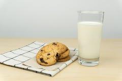 Sluit omhoog van de chocoladeschilferkoekjes en een glas melk stock fotografie