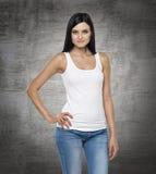 Sluit omhoog van de donkerbruine dame in een wit mouwloos onderhemd en jeans Stock Foto