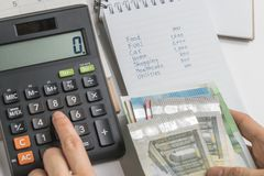 Sluit omhoog van de duwende knoop van de vrouwenhand op calculator met lijst van begroting, uitgave en kosten op kleine blocnote, stock afbeelding