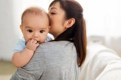 Sluit omhoog van de gelukkige zoon van de moeder kussende baby thuis royalty-vrije stock fotografie