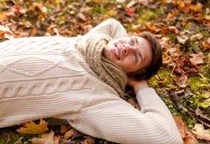 Sluit omhoog van de glimlachende jonge mens liggend in de herfstpark Stock Foto's