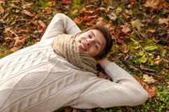 Sluit omhoog van de glimlachende jonge mens liggend in de herfstpark Stock Fotografie