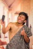 Sluit omhoog van de grappige voorhistorische mens die grappige gezichten doen aan de camera, die een selfie met zijn omhoog cellp Royalty-vrije Stock Afbeelding