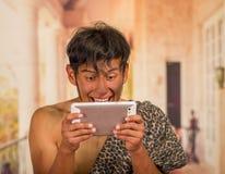 Sluit omhoog van de grappige voorhistorische mens die grappige gezichten doen die aan de camera, in zijn handen een tablet, in va Stock Fotografie