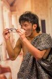 Sluit omhoog van de grappige voorhistorische mens die grappige gezichten doen aan de camera, in zijn handen die glazen, in vaag h Stock Foto