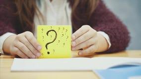 Sluit omhoog van de hand van een schoolmeisje op een onscherpe grijze achtergrond Heft een blad met de inschrijving van vele vraa stock video