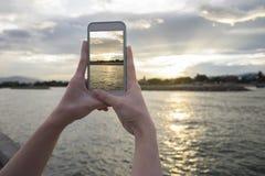 Sluit omhoog van de hand van de vrouw houdend slimme telefoon, mobiele, slimme telefoon over vage mooie overzees met zonsondergan Stock Fotografie